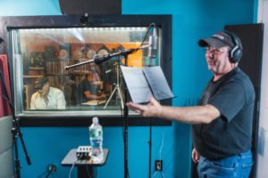 "Actor/Singer, Avi Hoffman at mic stand in recording studio, ""Boycott"" TV Series Show Creator, Jeff Mustard in B.g. at engineering board, through glass."