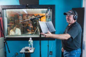 "Actor/Singer, Avi Hoffman at mic stand in recording studio, ""Boycott"" TV Series Show Creator, Jeff Mustard in B.g. at engineering board, through glass."