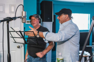 Writer/Producer, Jeff Mustard working with Actor/Singer, Avi Hoffman, in recording studio reviewing script for mustard's musical adaptation of his TV Series, Boycott.